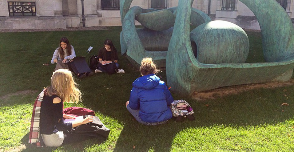 Students sketching in front of Henry Moore's sculpture 'Hill Arches' in the grounds of the Fitzwilliam Museum.